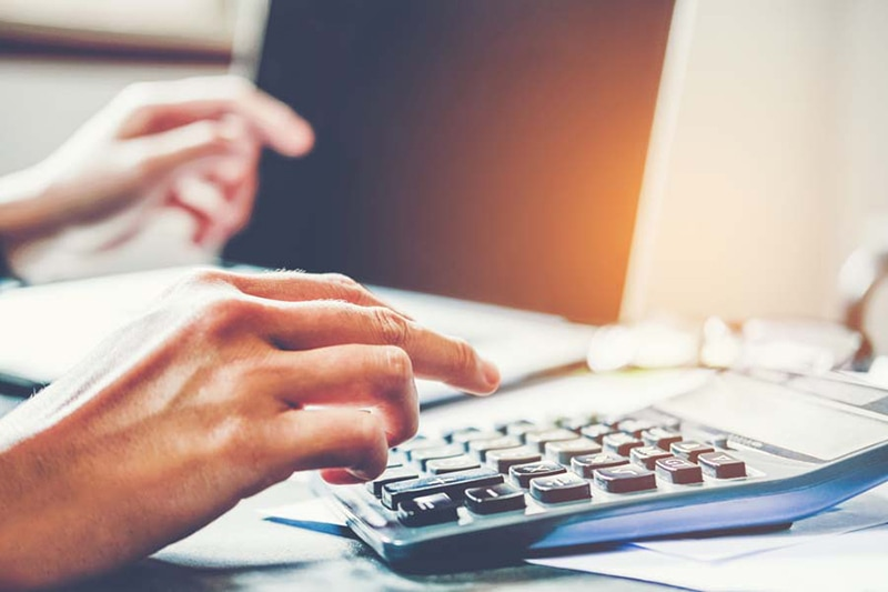 Hands typing on a calculator on an office desk, Common AC Purchasing Mistakes to Avoid | HVAC Installation | Johnstown