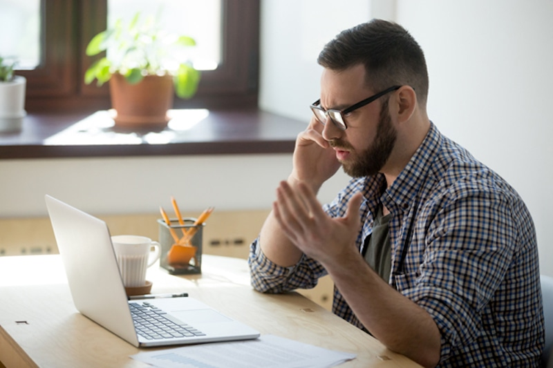 Frustrated male employee discussing contract details over the phone