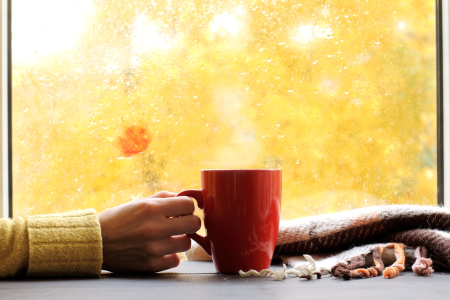 red mug of hot drink, when behind a window is rain in autumn in Altoona, PA